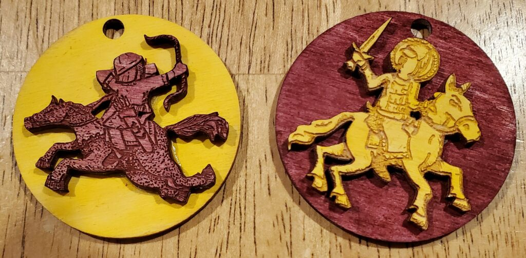 Two round wooden tokens lying on a wooden table top. On the left: a yellow disc with a red Mongolian horse archer, in relief. On the right: a red disc with a yellow Russian cavalryman brandishing a sword, in relief.